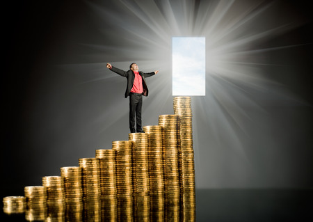 successfulness: businessman stand on top of  many rouleau gold  monetary  coin, on dark background