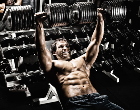 musculation: very power athletic guy ,  execute exercise press with  dumbbells, in gym