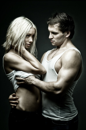 vehement: muscular handsome sexy guy with pretty woman, on dark background, glamour  light