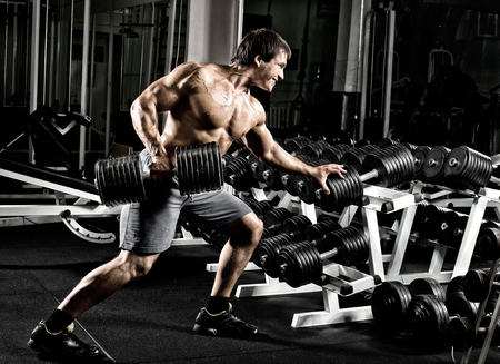 traction: very power athletic guy ,  execute  traction with  dumbbells, exercise on broadest muscle of back, in gym