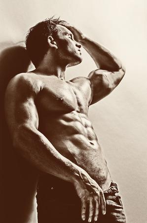 musculoso: el chico guapo sexy muy muscular en el fondo de la pared gris