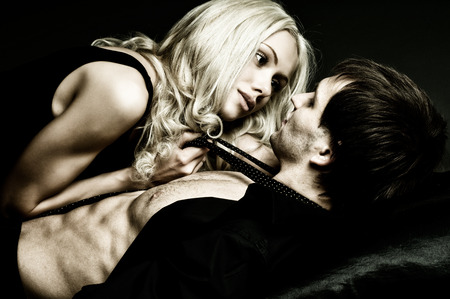 pareja apasionada: muscular guy sexy guapo con mujer bonita, sobre fondo oscuro, luz de glamour