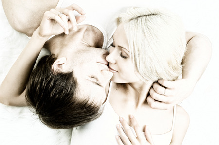 necking: very happy  pretty couple, smile and kiss,  lie on white fur, close up Stock Photo
