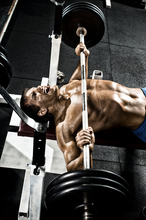 musculation: very power athletic guy ,  execute exercise press with weight, in gym