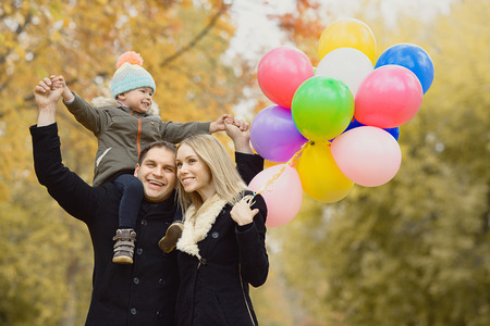 joyous festivals: happy family with little child and air-balloons, outing in autumn park Stock Photo