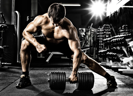 sports hall: very power athletic guy ,  execute  traction with  dumbbells, exercise on broadest muscle of back, in sport hall