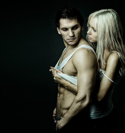 vehement: muscular handsome sexy guy with pretty woman, on dark background Stock Photo