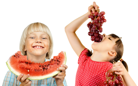 little boy and girl eating watermelon and grape, on white background, isolated photo
