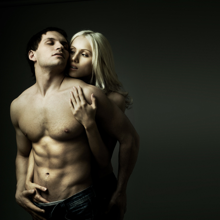 muscular handsome sexy guy with pretty woman, on dark background Stock Photo
