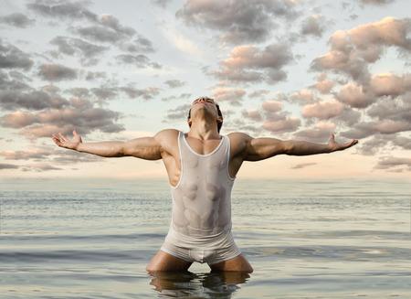 하늘과 바다 배경에 매우 근육질의 잘 생긴 섹시한 남자