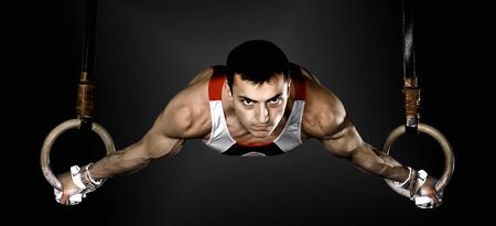 gimnasia: El deportista el chico, realiza ejercicio difícil, Gimnasia de deportes Foto de archivo