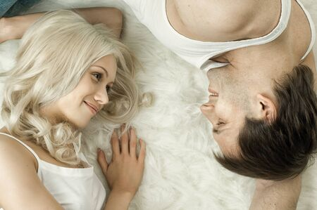 portrait happy  pretty couple, smile , look eyes to eyes,  lie on white fur, close face photo