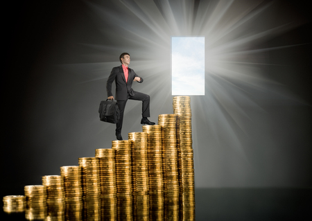 pecuniary: businessman stand on top of  many rouleau gold  monetary  coin, on dark background