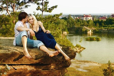 necking: romantic  date on nature, happy couple sit aloft on rock  with beautiful view