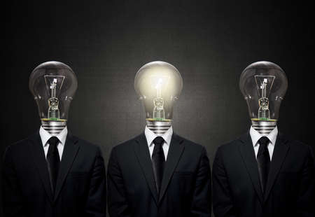careerist: group of three businessman with light electric bulb instead of head, on dark background, idea concept Stock Photo
