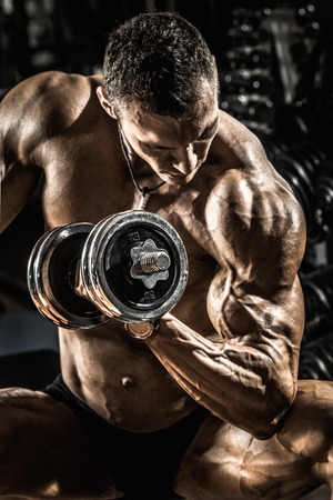 execute: very power athletic guy ,  execute exercise with  dumbbells, on bkack background Stock Photo