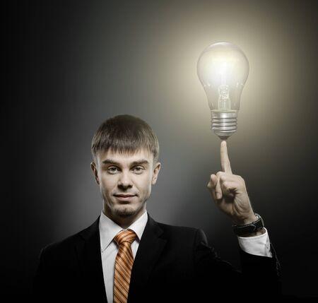 businesslike: handsome businessman index finger point upwards with light bulb, on dark background Stock Photo