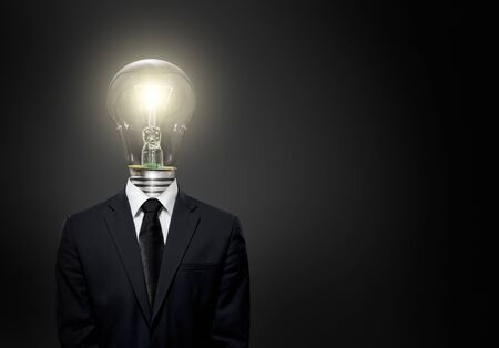 careerist: handsome businessman with light electric bulb instead of head, on dark background