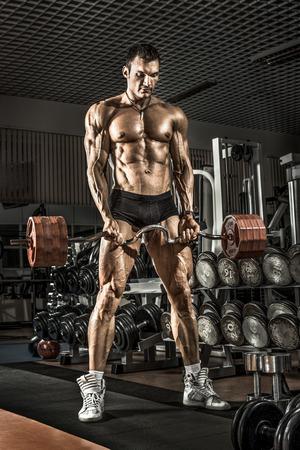 brawny: very power athletic guy ,  execute exercise with  dumbbells, on bkack background Stock Photo