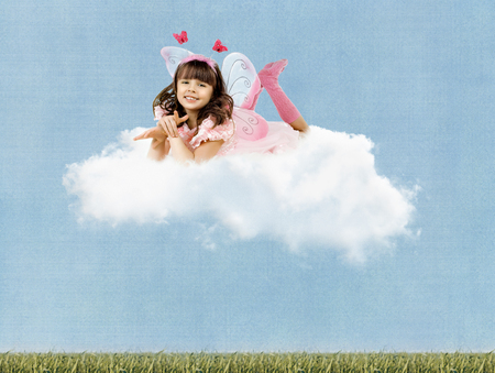collage, beautiful fun little girl with wings , lie on clouds and  smile on sky background photo