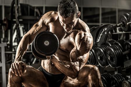 musculation: very power athletic guy ,  execute exercise with  dumbbells, on bkack background, horizontal photo Stock Photo