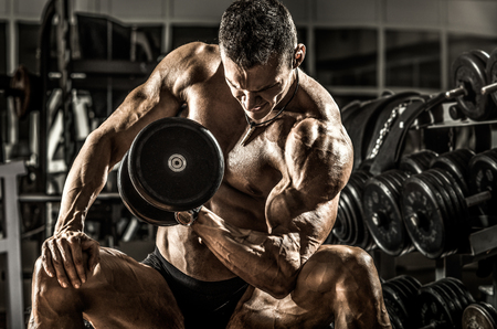 very power athletic guy ,  execute exercise with  dumbbells, on bkack background, horizontal photo Stock Photo