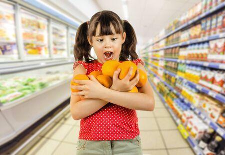 citrous: beauty little girl hold many orange and amazed, on shop background Stock Photo