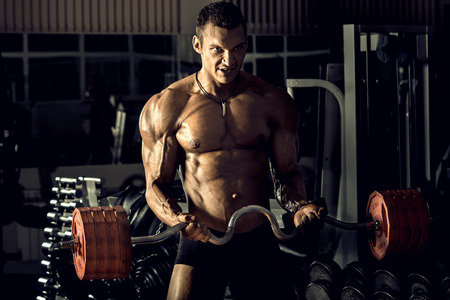 musculation: very power athletic guy ,  execute exercise with weight, on bkack background, horizontal photo