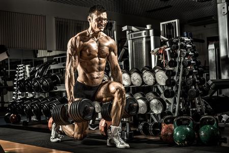 bodybuilder: chico atlético poder muy, ejecutar ejercicios con pesas, en el gimnasio