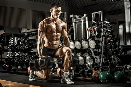 gym: very power athletic guy ,  execute exercise with  dumbbells, in gym