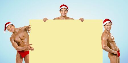 group of men: three muscular  bronzed handsome sexy Santa Claus, look out from board and smile Stock Photo