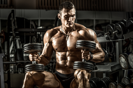 very power athletic guy bodybuilder , sit with  dumbbells, in dark gym Foto de archivo