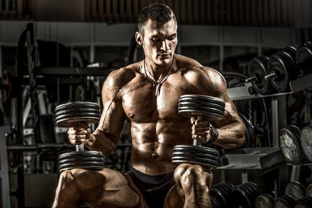 very power athletic guy bodybuilder , sit with  dumbbells, in dark gym Archivio Fotografico