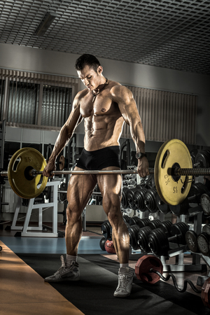 musculation: guy bodybuilder , execute exercise with weight in gym, vertical photo Stock Photo