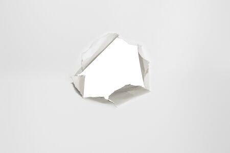 rupture: scrap of paper, on white sheet, horizontal photo
