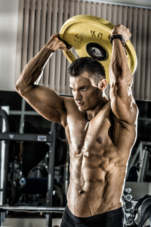 guy bodybuilder , execute exercise with weight in gym, vertical photo Stock Photo