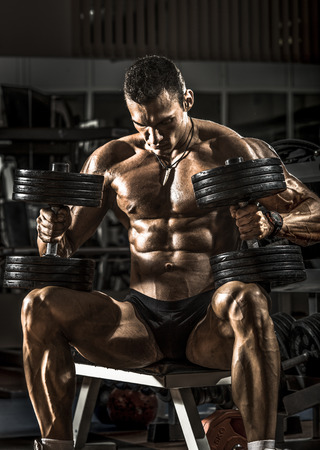 men at work: very power athletic guy bodybuilder , sit with  dumbbells, in dark gym Stock Photo