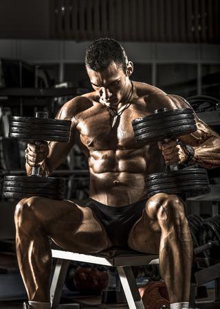 bodybuilder: very power athletic guy bodybuilder , sit with  dumbbells, in dark gym Stock Photo