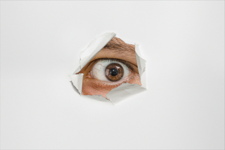 furtively: eye peep through hole on paper white sheet, close up horizontal photo