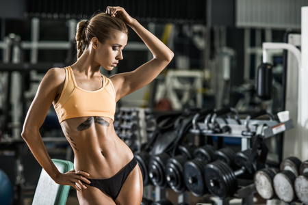 woman muscle: young fitness woman in gym, horizontal photo