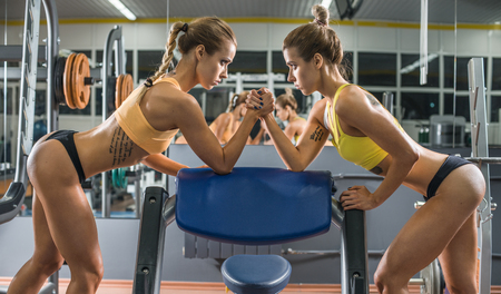 female wrestling: two young fitness woman, arm wrestling in gym, horizontal photo