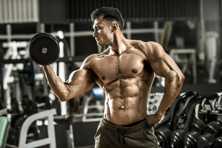 musculation: very power athletic guy , execute exercise with  dumbbells, inside gym, horizontal photo Stock Photo