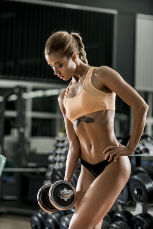 musculation: young fitness woman execute exercise with dumbbells in gym, vertical photo