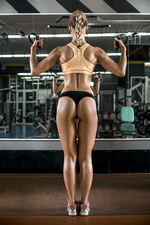 musculation: young fitness woman execute exercise with exercise-machine Cable Crossover in gym, vertical photo