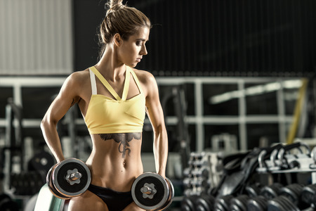 girl sport: young fitness woman execute exercise with dumbbells in gym, horizontal photo