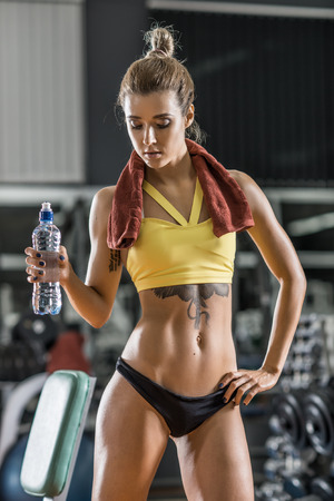 brawny: young fitness woman with bottle water in gym, vertical photo