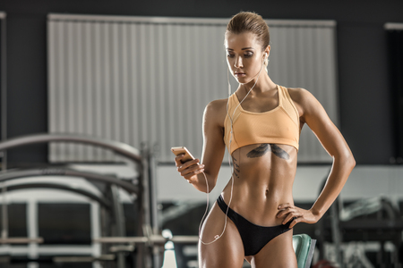 musculation: young fitness woman tired in gym and listen music with headset