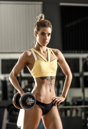 vertical: aptitud de la mujer joven y ejecutar ejercicios con pesas en el gimnasio, la foto vertical