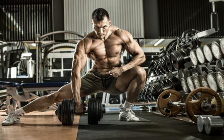 bodybuilder: hombre culturista, ejecutar ejercicios con pesas, en el interior gimnasio, foto horizontal