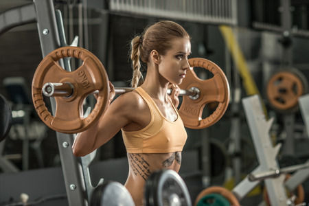 tough girl: young fitness woman execute exercise with weight in gym, horizontal photo